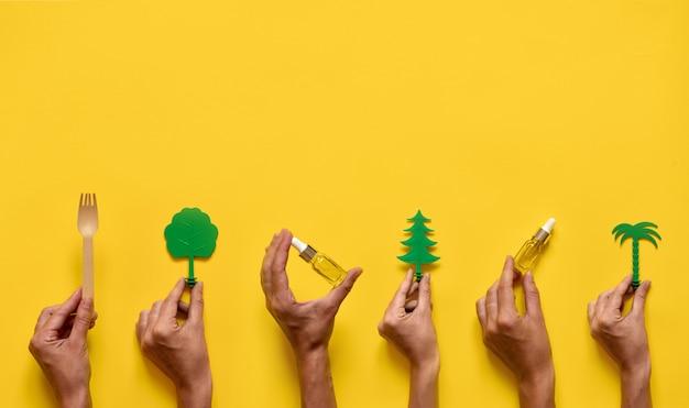 エッセンシャルオイルと木を持っている手。自然医学フラットレイアウト。黄