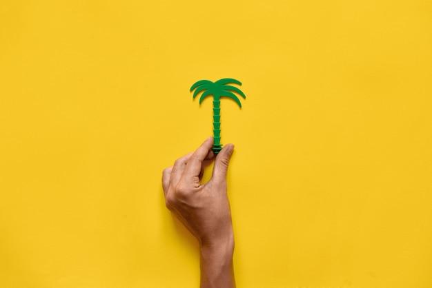 ヤシの木のプラスチックのおもちゃを持っている手。黄 。夏の旅行。エコロジーのアイデア。コピースペース
