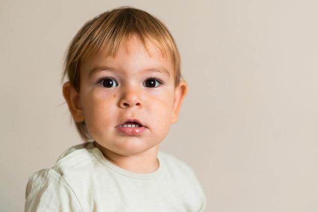 白い背景で隔離のかわいい男の子の肖像画