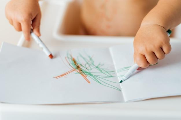 カラフルなマーカーで紙に描く小さな子供の手のクローズアップ。創作活動