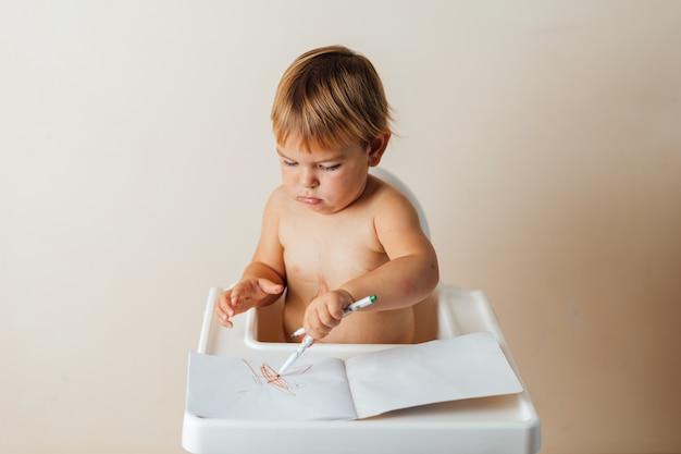 小さな幼児の赤ちゃんが紙にカラフルな線を描くフェルトペンで遊ぶ