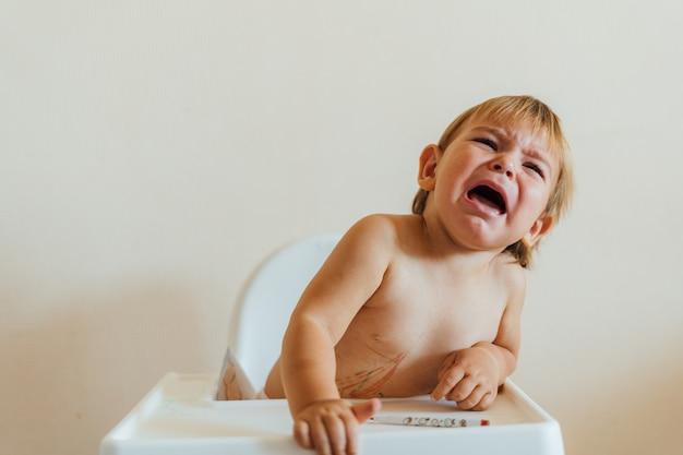 ハイチェアに座って叫んでいる幼児の赤ちゃん。メルトダウンの問題。食べ物を拒否