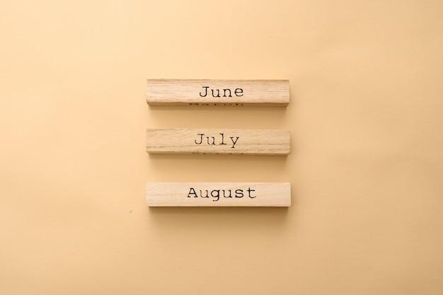 木製キューブの木製カレンダー夏の数ヶ月。
