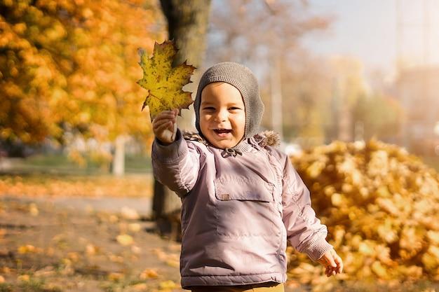 Улыбающийся ребенок с букетом желтых кленовых листьев в осеннем парке