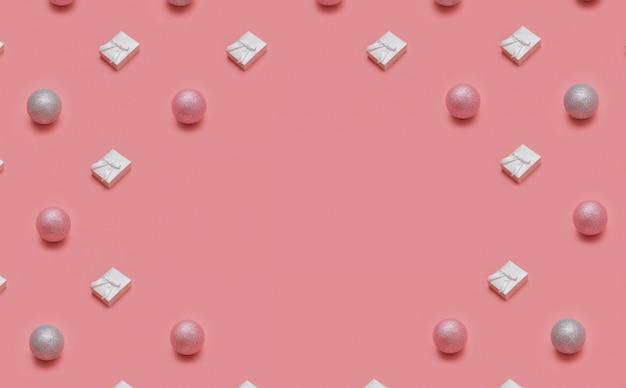 ピンクの背景にさまざまな冬と新年のオブジェクトで作られたトレンディなクリスマスパターン