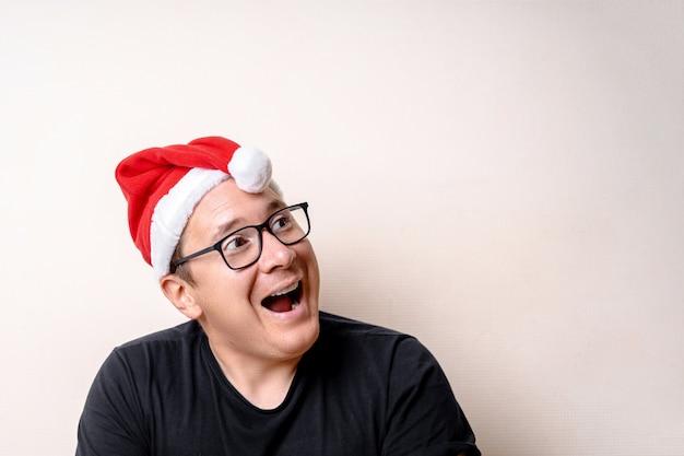 白い壁にクリスマス帽子を持つ面白い若者。悲しいサンタ。クリスマス
