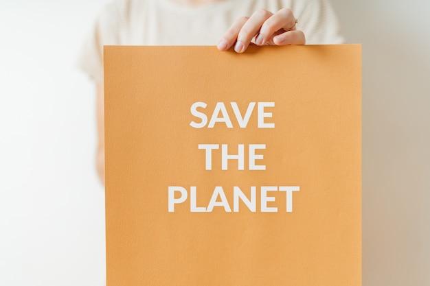 Спасите планету - экологический знак протеста за зеленое будущее планеты. женщина, держащая бумагу