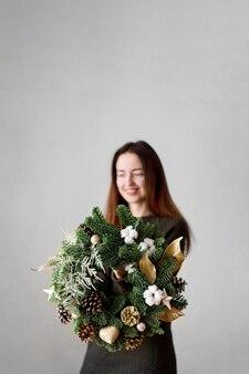 女性の手に緑のクリスマスリース。白い表面に最小限。季節の装飾。スペースをコピーします