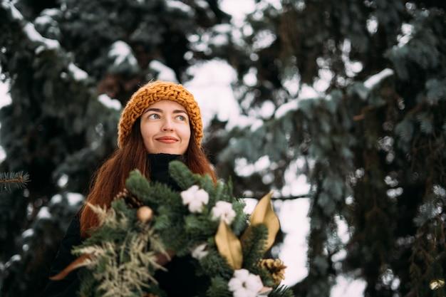 Портрет образа жизни усмехаясь тысячелетней девушки в оранжевой шляпе. снежное рождество