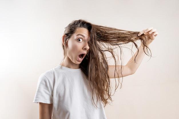 Красивая кавказская девушка с влажной грязной крепко после ванны. проблема тонких волос. изолированные