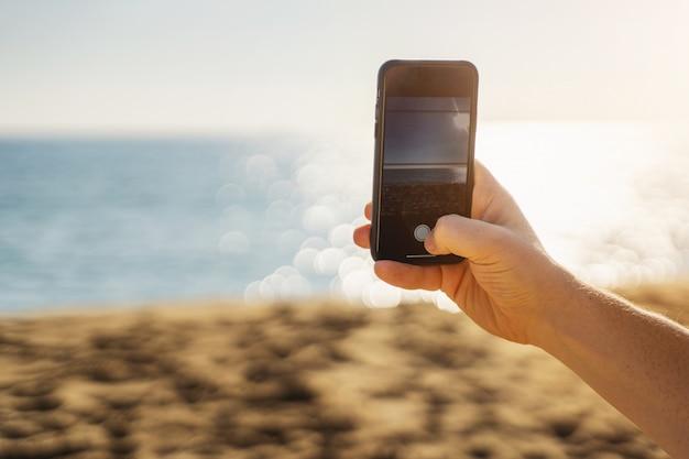 スマートフォンを押しながら海の写真を作る男の手。夏休みの写真