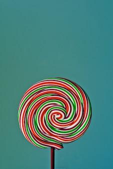 緑の背景にスパイラル形状のカラフルなロリポップ