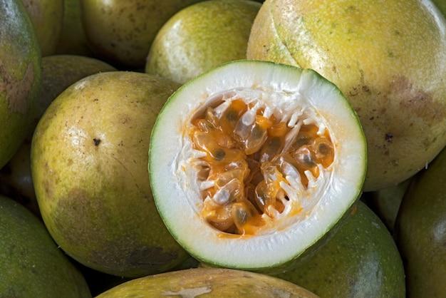 全体の果物の山の上に酸っぱいパッションフルーツをスライス
