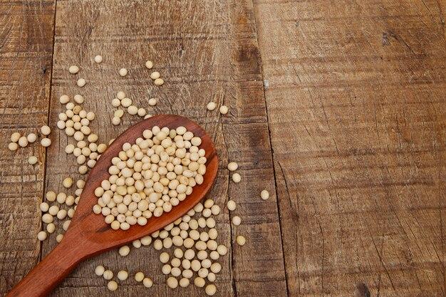 テキスト用の領域と木のスプーンの大豆