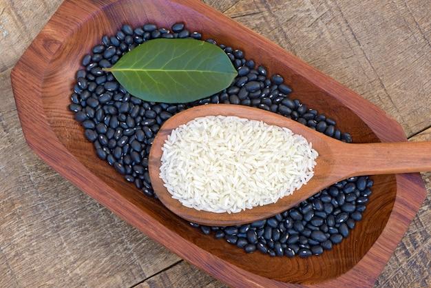 豆と木製の大皿に生のご飯スプーン