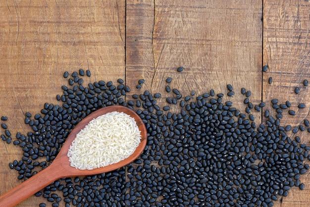 豆のヒープ上の生米と木のスプーン