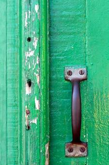 閉じた緑色のアンティークドアのロックとノブ