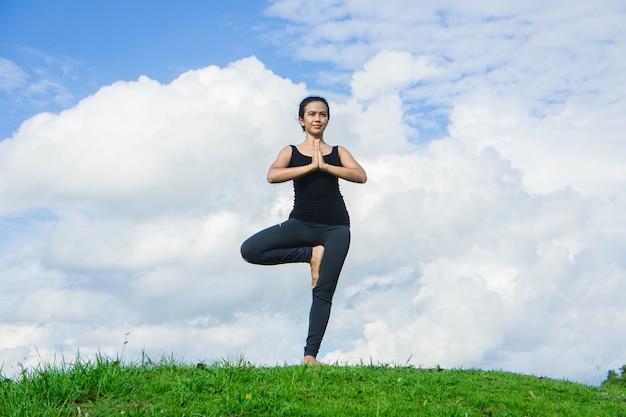 ヨガを練習する女性は、自然と青空の背景でリラックスします。