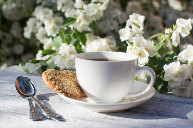 Белая фарфоровая чашка с чаем и двумя овсяным печеньем с кунжутом на деревянном столе на фоне цветущего жасмина.
