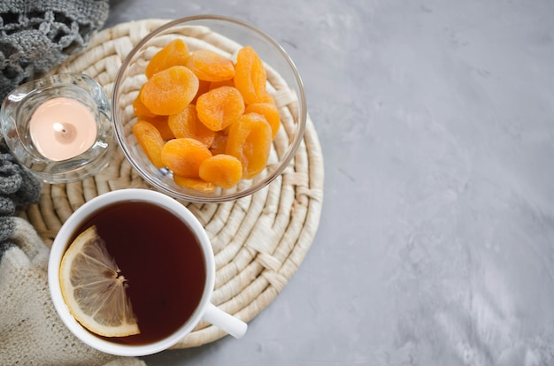 一杯の紅茶とテーブル、キャンドル、ニット毛布の上のドライアプリコット。