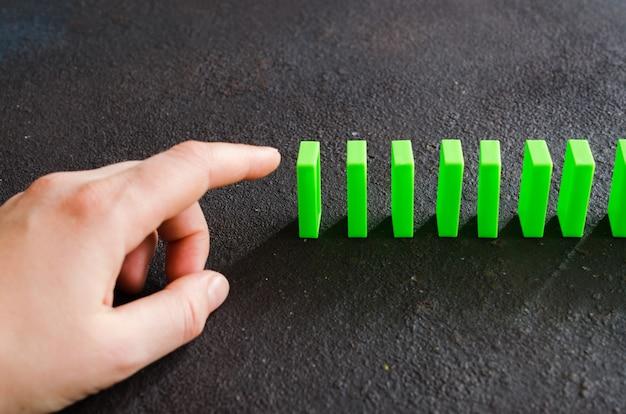連鎖反応を引き起こすためにドミノの部分を押す準備ができている手。