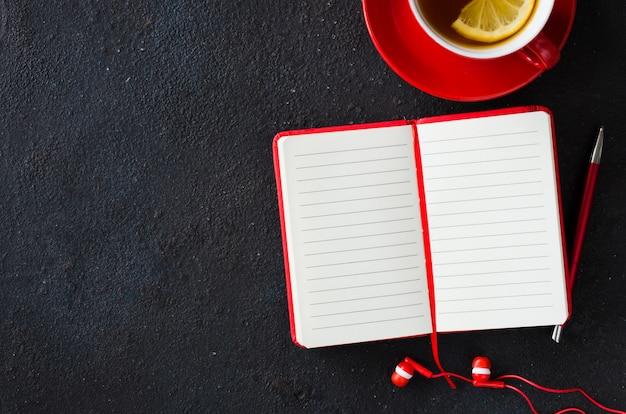 Пустой красный ноутбук, компьютер ноутбук, наушники и чашка чая.