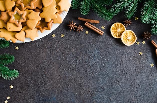 Кулинарный фон с свежеиспеченный рождественские пряники, специи и еловые ветки.