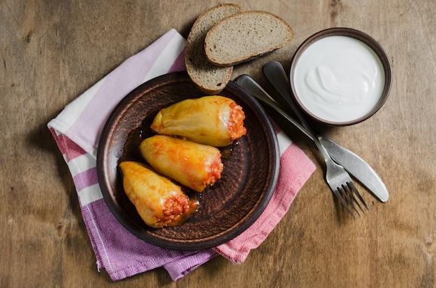 トマトとライ麦パンにご飯とひき肉のシチューを詰めたピーマン。素朴な食べ物。