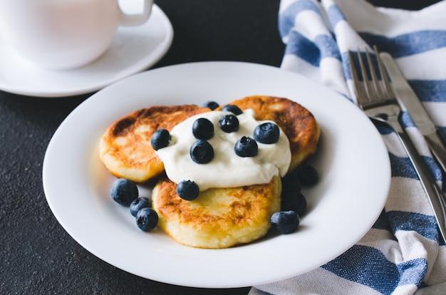 Сырники на завтрак с йогуртом и черникой.