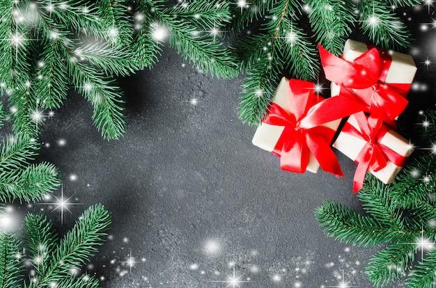 Подарки на рождество и ель на темной предпосылке.