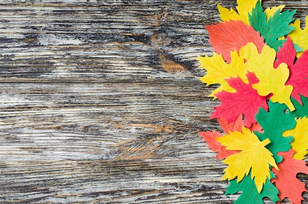 ペーパークラフト、赤と黄色の紅葉。フラットの平面図は、ヴィンテージの木製の背景に横たわっていた。