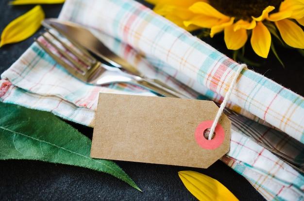 空のタグ、ナプキン、ひまわりとカトラリーと秋のテーブルの場所の設定。