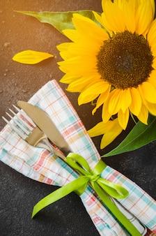 Осенняя сервировка стола, столовые приборы с салфеткой и подсолнечника.