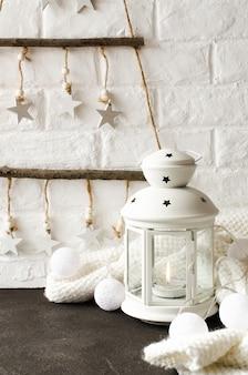 スカンジナビアの居心地の良い家の装飾。木製のクリスマスツリー、白いランタン、スカーフ、クリスマスガーランド。