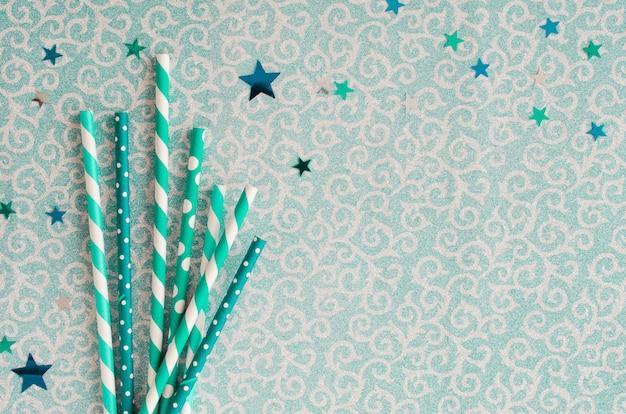 緑色の光沢のある背景のエコフレンドリーな紙ストロー。お祭りのコンセプト。