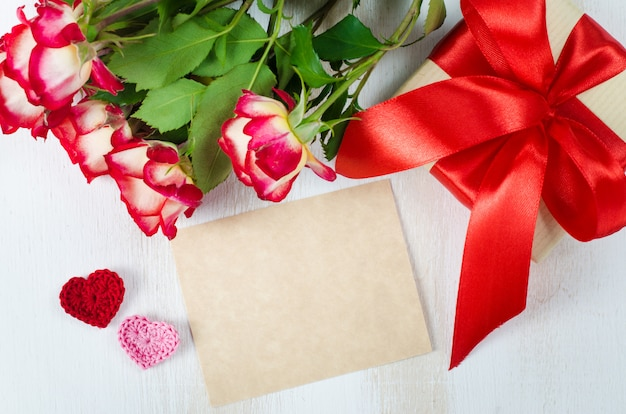 空のグリーティングカード、赤いバラとギフトボックス