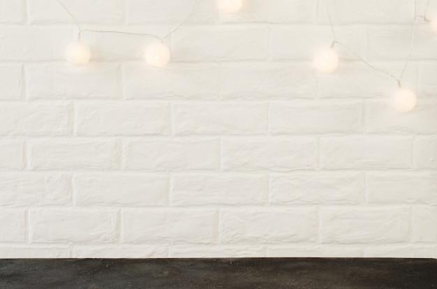 クリスマスライトの背景を持つ白いレンガの壁