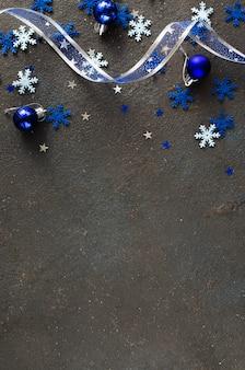 Синий новогодний фон. кудрявая лента с декоративными шарами и снежинками.
