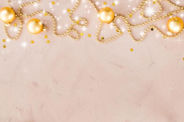 Золотой новогодний фон. бусы с декоративными шариками и звездами.