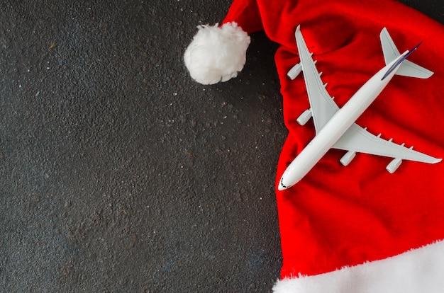 旅行またはクリスマス旅行の計画。おもちゃの飛行機と暗いコンクリートのサンタ帽子。