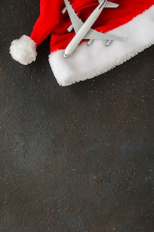 クリスマスや新年の旅行の概念。おもちゃの飛行機と暗いコンクリートのサンタ帽子。