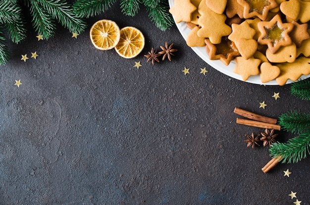 Кулинарный фон с свежеиспеченный рождественские пряники, специи и еловые ветки. копировать пространство