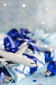 Рождество или новый год путешествия концепция. игрушечный самолет с паспортами и подарочной коробкой