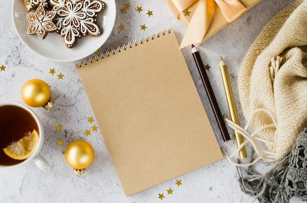 ギフトボックス、紅茶、クッキー、格子縞の空白の茶色のノートブックのフラットレイアウト。