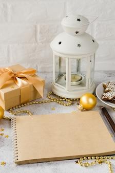 茶色のノートブック、ギフトボックス、ジンジャーブレッドクッキー、ランプとクリスマス組成。