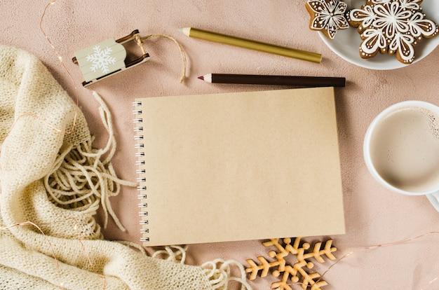 クリスマスの装飾と格子縞の空白の茶色のノートブックのフラットレイアウト。