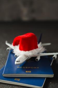 クリスマスや新年の旅行の概念。パスポートとサンタクロースの帽子とおもちゃの飛行機。