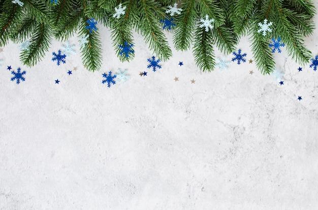 モミの枝と灰色のコンクリートの青いつまらない新年のクリスマス。