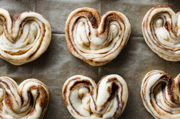 生の未焼成パン。ベーキングペーパーに砂糖とシナモンの酵母パンをクローズアップ。