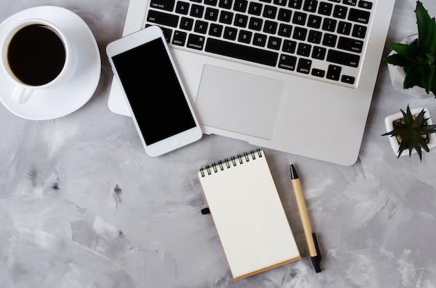 ノートパソコンと一杯のコーヒーをオフィスの机の上の黒い空白の画面と白いスマートフォン。電話のモックアップ。